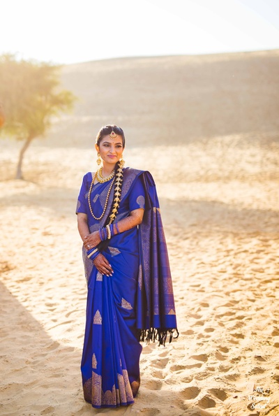 The bride looks gorgeous in a blue and gold kanjeevaram saree.