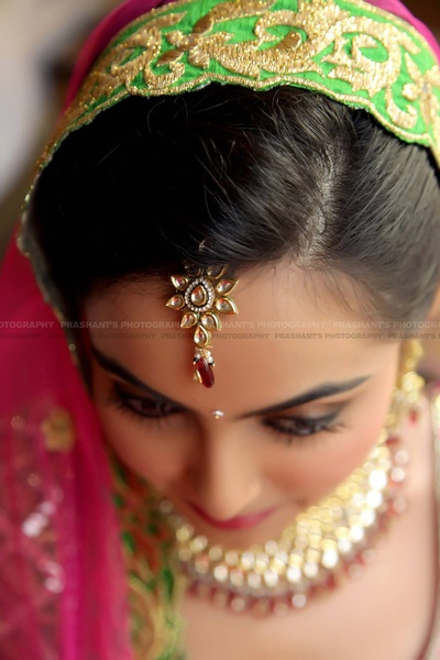 Floral shaped maangtikka studded with kundan stones and a red stone drop