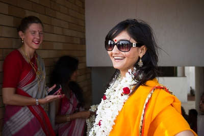 Marigold yellow saree adorned with a garland made with Rajnigandha and red handmade flowers