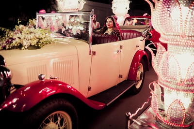 Here comes the bride in her vintage car