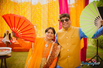 Yellow and pink themed haldi ceremony with paper hand fans for the outdoor ceremony
