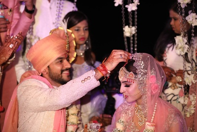 The groom putting on sindoor over the bride's forehead