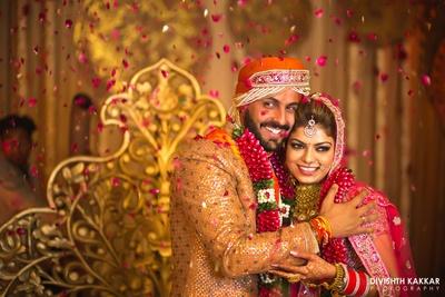 Varmala ceremony! Bride and groom wearing beautiful flower garlands.