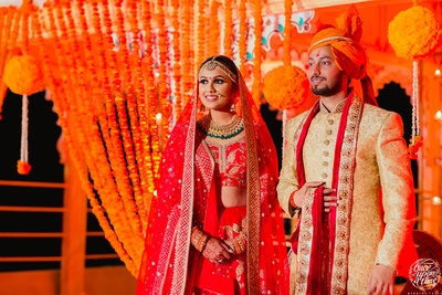 A grand picture of the bride and groom against a genda phool decor