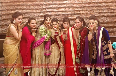 Bridesmaids dressed in vibrant outfits are blowing kisses in style