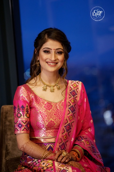 the bride looks stunning in this traditional pink banarasi saree, paired with ethnic gold jewellery.
