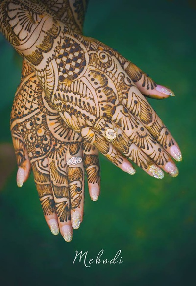 Detailed and intricately patterned mehendi design enriched with glittering nail art