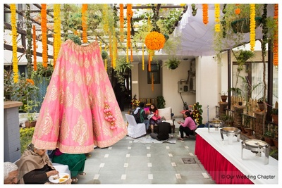 Pink flared wedding lehenga styled with woven motifs and matching pom-poms