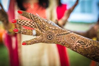 Intricately designed indian bridal mehendi adorned with blood red painted nails and silver diamond studded ring