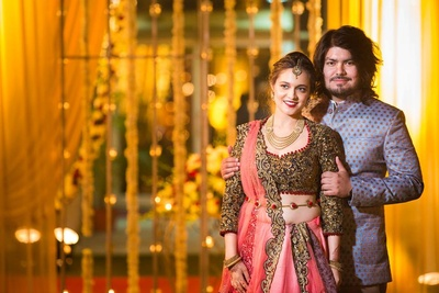 Kriti in peach pink lehenga with heavy zari worked blouse and Rohan in blue bandhgala for their Wedding reception.