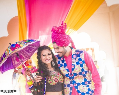 A cheerful couple in attractive attires celebrating mehendi in a bright sunny day