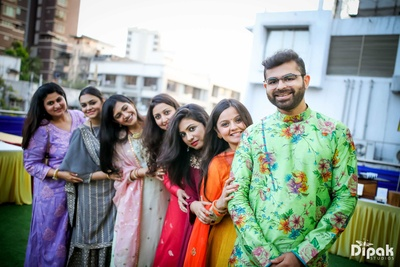 Groom and bridesmaids posing together during the mehndi function