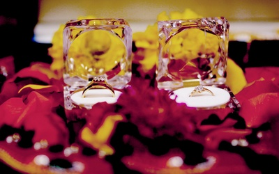 Engagement rings creatively presented in transparent boxes on a bed of rose petals