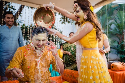 the bride and groom having fun at the haldi ceremony