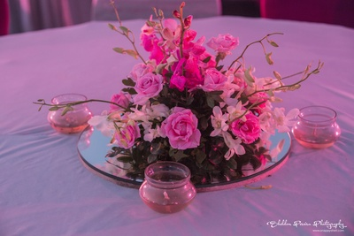 Table centrepiece with glass lamps and bunch of flowers