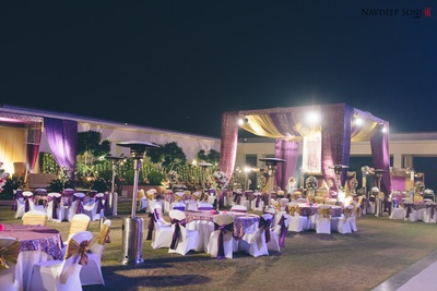 Gold and purple themed evening decor setup with tie-backs, clustered floral arrangement and drapes