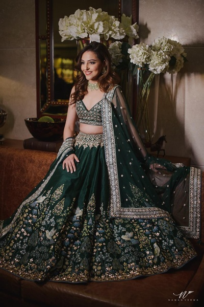 Benaisha Kharas in an emerald green lehenga embellished with intricate, hand painted pichhwai work by Anita Dongre for her sangeet