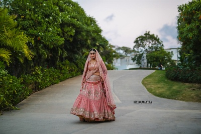 the beautiful bride in a coral lehenga for her wedding ceremony