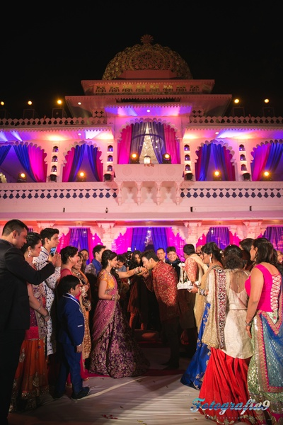 Couple dressed in complementing pink and red outfits for their pink and blue themed sangeet ceremony