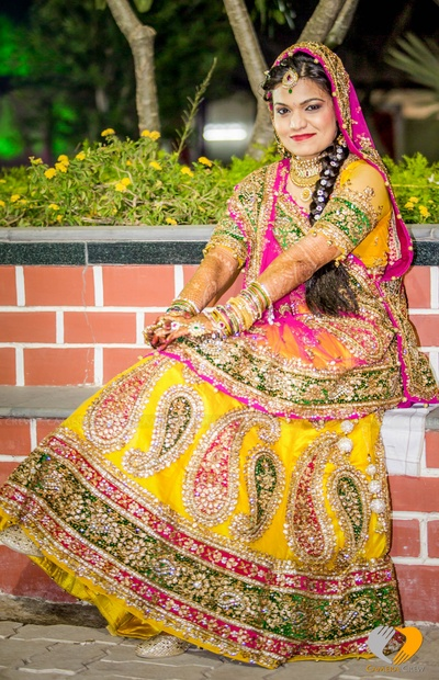 Heavily embellished and embroidered yellow and pink bridal lehenga