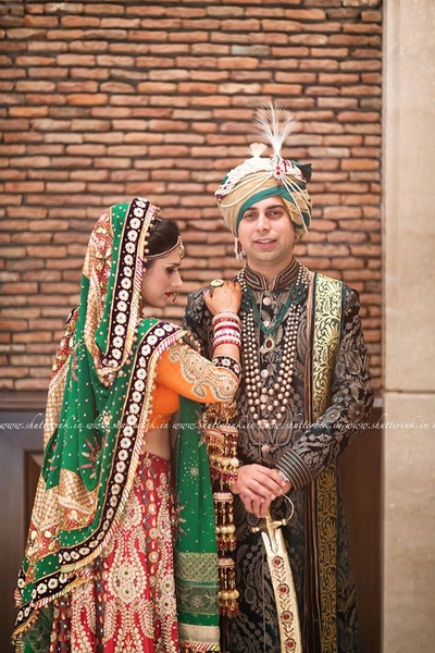 Mixed match wedding lehenga, in tones of red, orange and green. Heavily embellished with gotta patti motifs