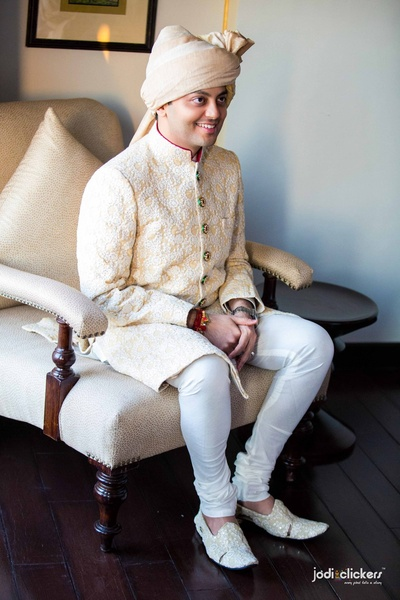 Buttery yellow wedding sherwani embellished with white resham embroidery, green round button details and gold Safa