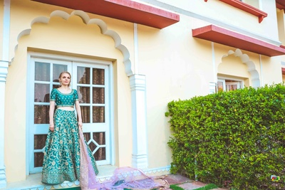 Megan poses in her teal blue lehenga with a contrast pink dupatta