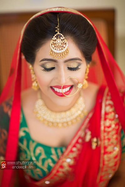 Bride shinning from every angle with metallic makeup, highlighting the smokey eye-makeup and hot red lipstick