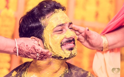 Haldi being applied to Sahil's face.