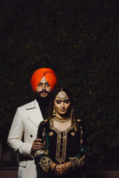 A regal shot of the stunning bride in her velvet oufit and the groom in a debonair trenchcoat