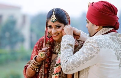 The couple share a romantic moment, wile the groom tries to adjust her earrings.