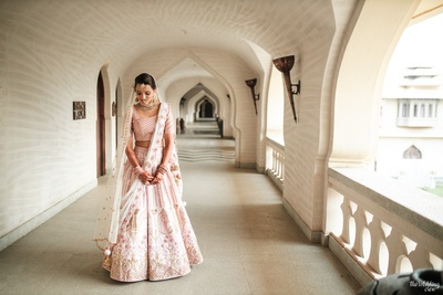 the bride in a customised pink lehenga for her wedding