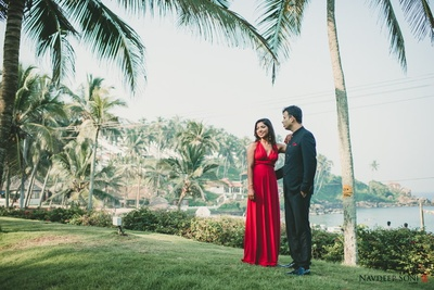 Blood red deep  V-necked floor length solid gown styled with minimal jewellery and makeup for the pre wedding photo shoot