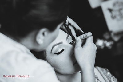 Black and white shot of bride getting her makeup done.
