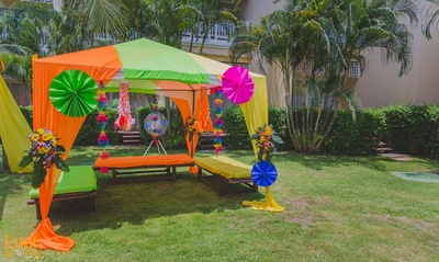Cabana styled outdoor wedding decoration with paper fans, clustered floral arrangement and decorative strings