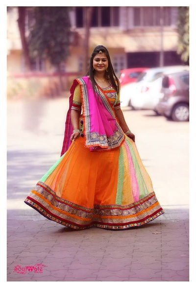 Bright orange bridal lehenga featuring colourful kalis, along with a patterned fancy blouse.