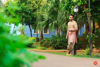 Wearing peach and pink shaded sherwani filled with gold zardozi work paired with beige patiala.