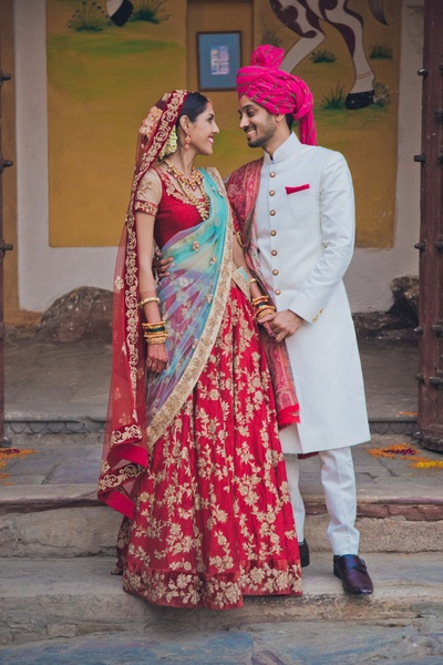 Red flared bridal lehenga embellished with gold floral embroidery and beads styled with double styled red and blue dupatta