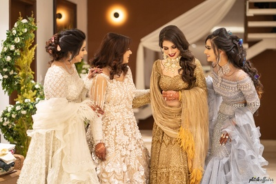 The bride and her bridesmaids look stunning in their pastel-hued outfits.