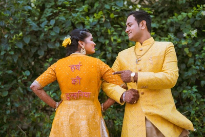 The bride shows off her innovative and customized blouse with her groom's name on it!