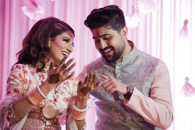 The bride and groom share a delightful moment at the mehendi ceremony!