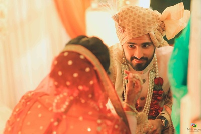 Candid moment captured between bride and groom at the wedding mandap