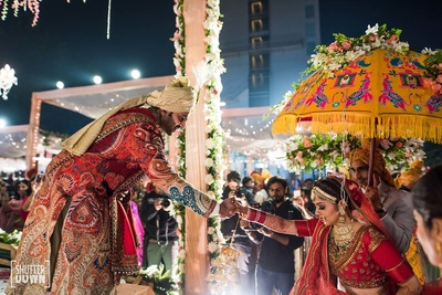 Groom helps the bride up on the mandap at Hotel Renaissance, Lucknow