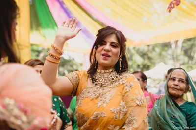Mother of the bride dancing in a yellow saree at the mehndi ceremony