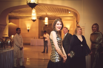 Bride's sister donning a beautiful gold and black dress for the welcome dinner party