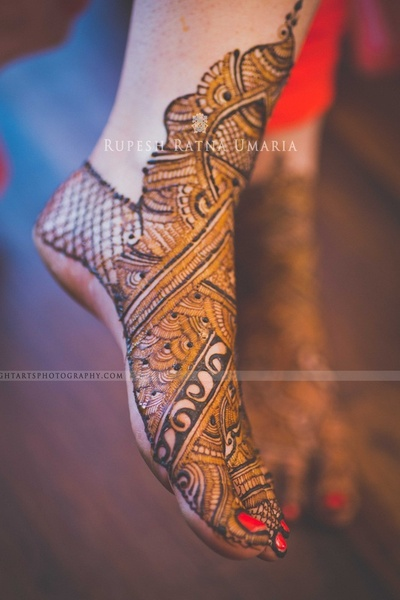 Feet covered in intricately patterned mehendi designs adorned with red nail paints