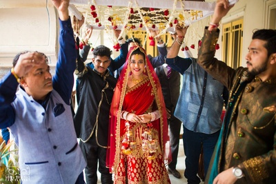 Real Bride Dipika in her regal red bridal lehenga being escorted to the mandap