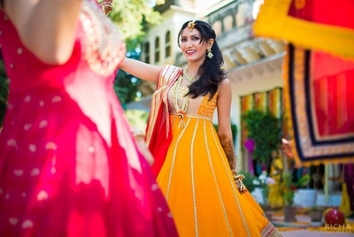 Dressed in an amber and red anarkali for her mehendi ceremony, styled with fresh flower jewellery