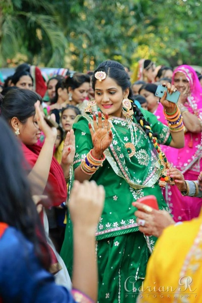 Traditional green ghagra with gold motifs and matching jewellery