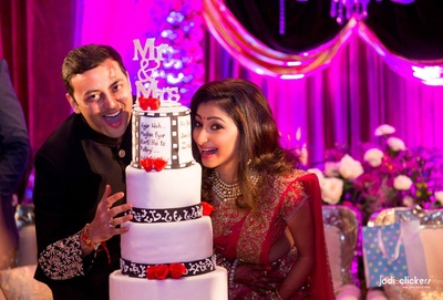Bollywood inspired three tier white, black and red wedding cake with a cake topper
